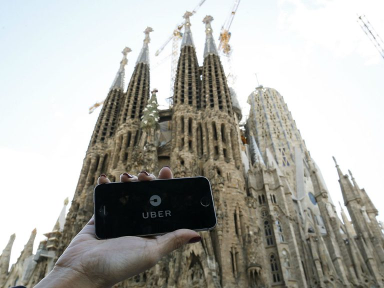 Un smartphone avec l'application de VTC Uber devant la Sagrada Familia à Barcelone. Photo: Pau Barrena/AFP